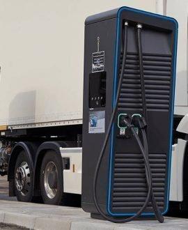 Camión en una electrolinera. Donde se ven dos cargadores eléctricos de color azul. TSB transporte y logística